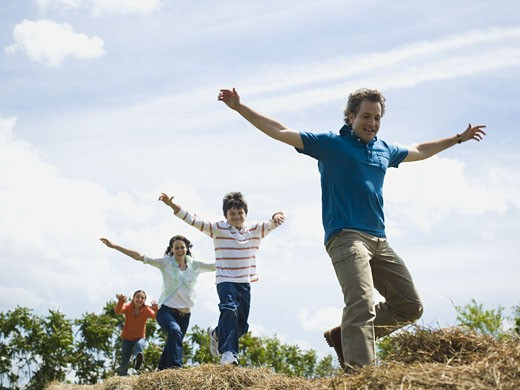 Low angle view of a man and a woman jumping with their children on hay bales : Stock Photo