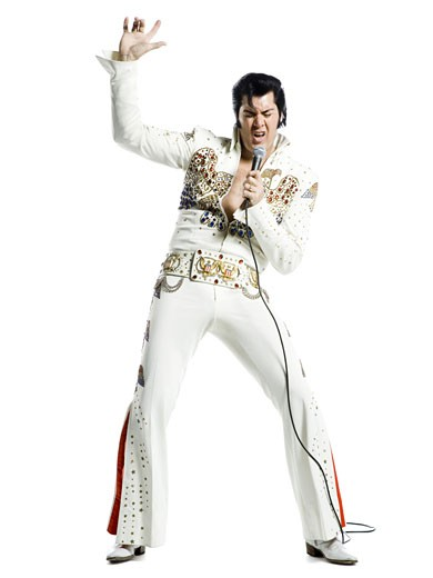 An Elvis impersonator singing into a microphone : Stock Photo