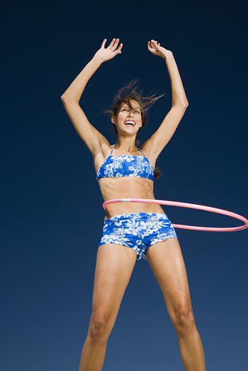Young woman playing with a hula hoop : Stock Photo