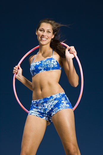 Portrait of a young woman holding a hula hoop and smiling : Stock Photo