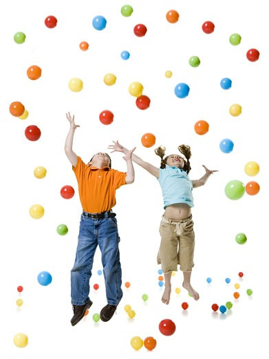 A boy and a girl playing with colored balls : Stock Photo