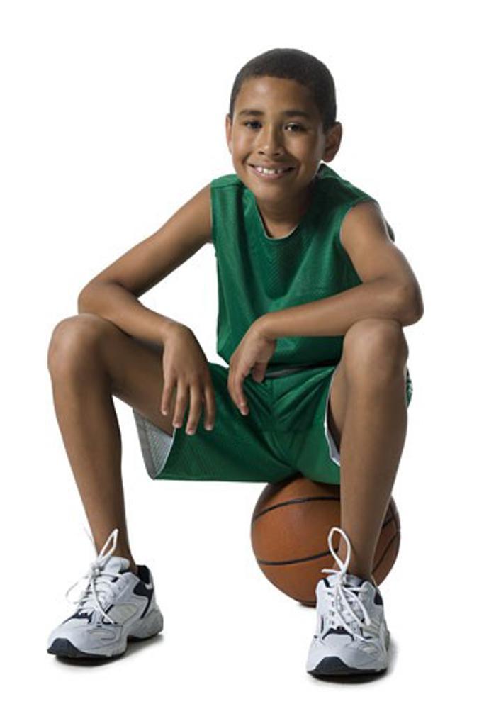 Portrait of a boy sitting on a basketball : Stock Photo