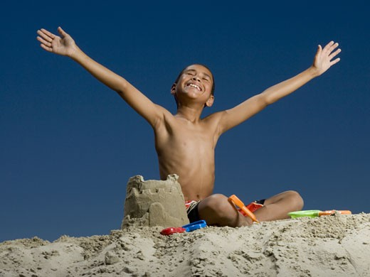 Stock Photo: 1660R-12989 Low angle view of a boy sitting beside a sand castle with his arms outstretched