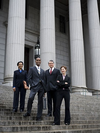 Stock Photo: 1660R-13099 Low angle view of lawyers standing on the steps of a courthouse