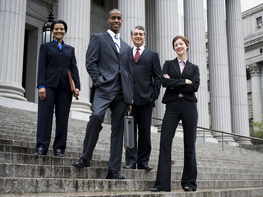 Stock Photo: 1660R-13100 Low angle view of lawyers standing on the steps of a courthouse