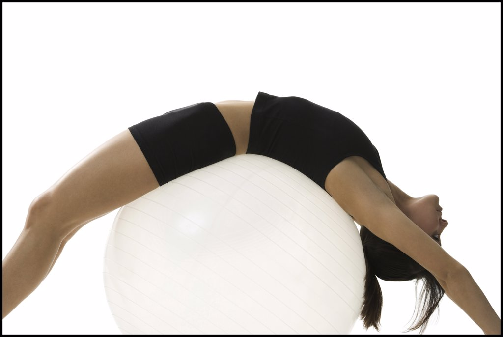 Profile of a mid adult woman exercising on a fitness ball : Stock Photo