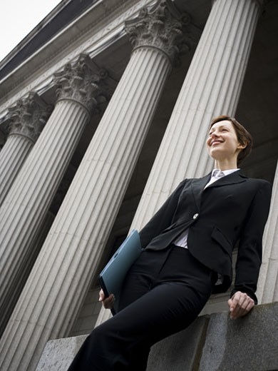 Low angle view of a female lawyer holding a file and smiling : Stock Photo