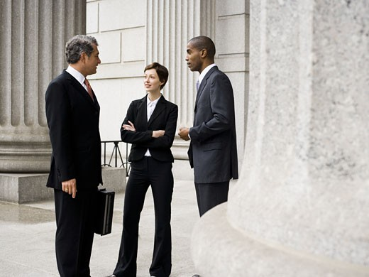 Three lawyers talking in front of a courthouse : Stock Photo