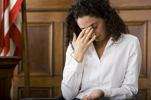 Stock Photo: 1660R-13136 An upset female witness sitting in a courtroom