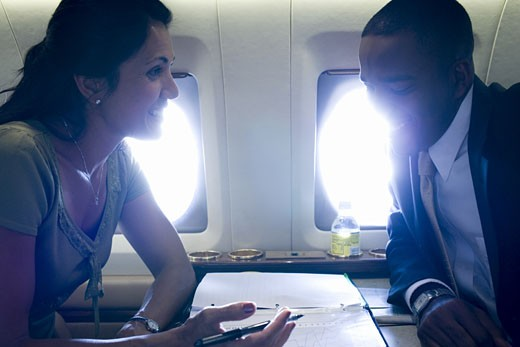 Stock Photo: 1660R-13198 A businesswoman and a businessman sitting face to face in an airplane and talking