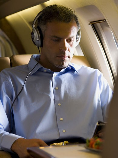 Stock Photo: 1660R-13215 A businessman listening to music on headphones in an airplane