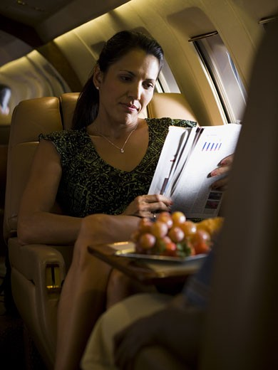 Stock Photo: 1660R-13220 A businesswoman reading a magazine on an airplane