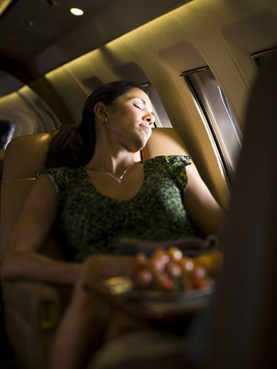 Stock Photo: 1660R-13221 A businesswoman sleeping on an airplane