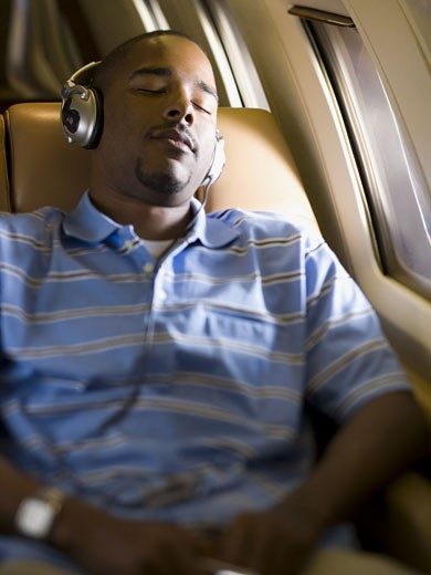 Stock Photo: 1660R-13225 A man listening to music on headphones in an airplane