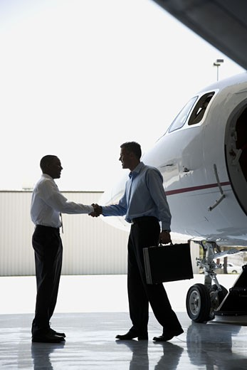 Stock Photo: 1660R-13234 Profile of two businessmen shaking hands near an airplane