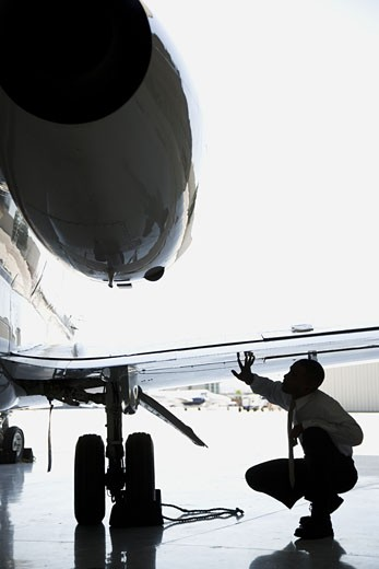 Businessman crouching and inspecting an airplane wing : Stock Photo