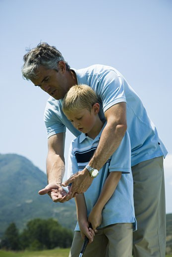 Father teaching his son to play golf : Stock Photo