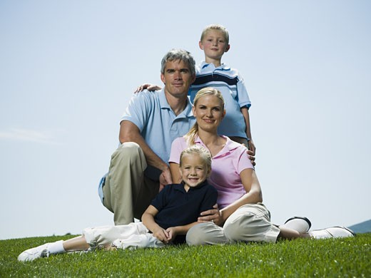 Stock Photo: 1660R-13304 Low angle view of parents and their two children sitting on grass