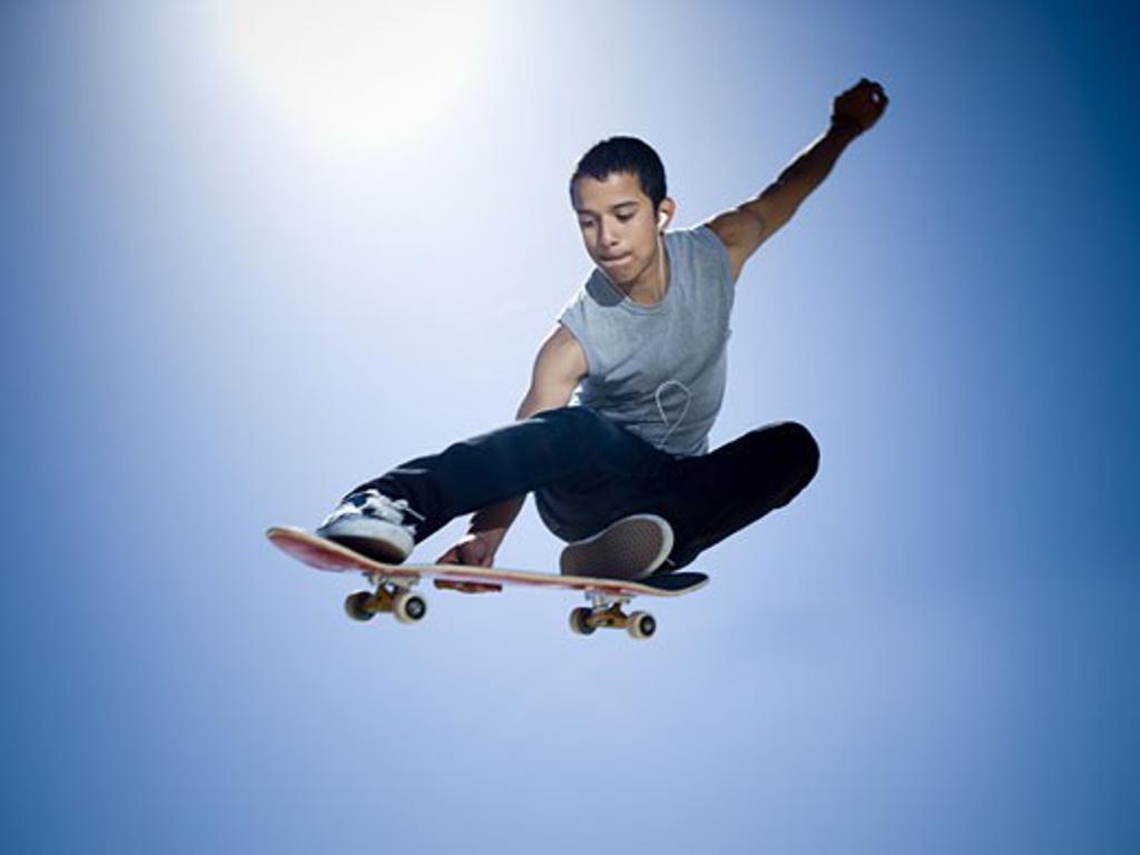 Low angle view of a teenage boy skateboarding : Stock Photo