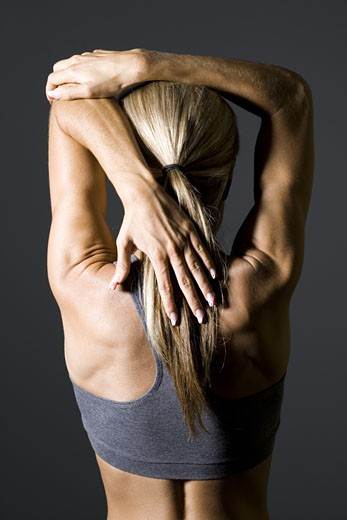 Rear view of a young woman exercising : Stock Photo
