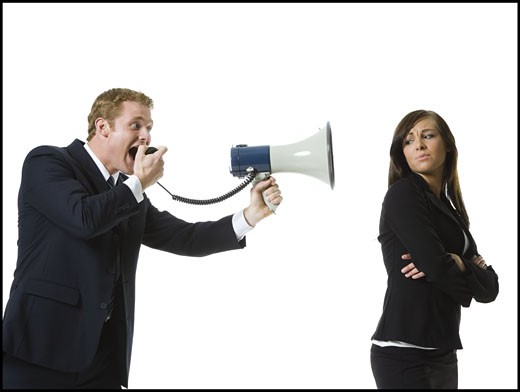 Profile of a businessman shouting into a megaphone with a teenage girl back : Stock Photo