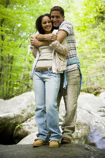 Portrait of a young couple embracing each other and smiling : Stock Photo