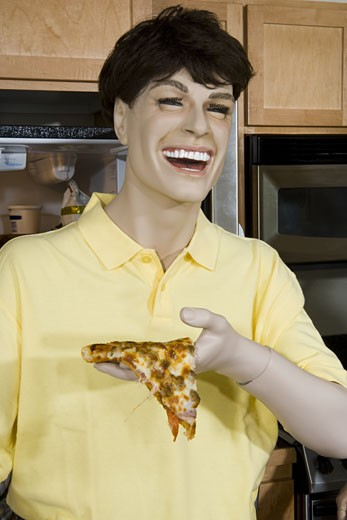 Close-up of a male mannequin holding a piece of pizza and laughing : Stock Photo