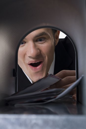 Close-up of a businessman looking into a mailbox : Stock Photo