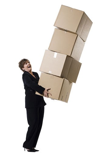 Profile of a senior woman holding a stack of cardboard boxes : Stock Photo