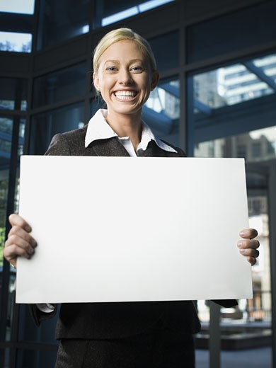 Portrait of a businesswoman holding a blank sign and smiling : Stock Photo
