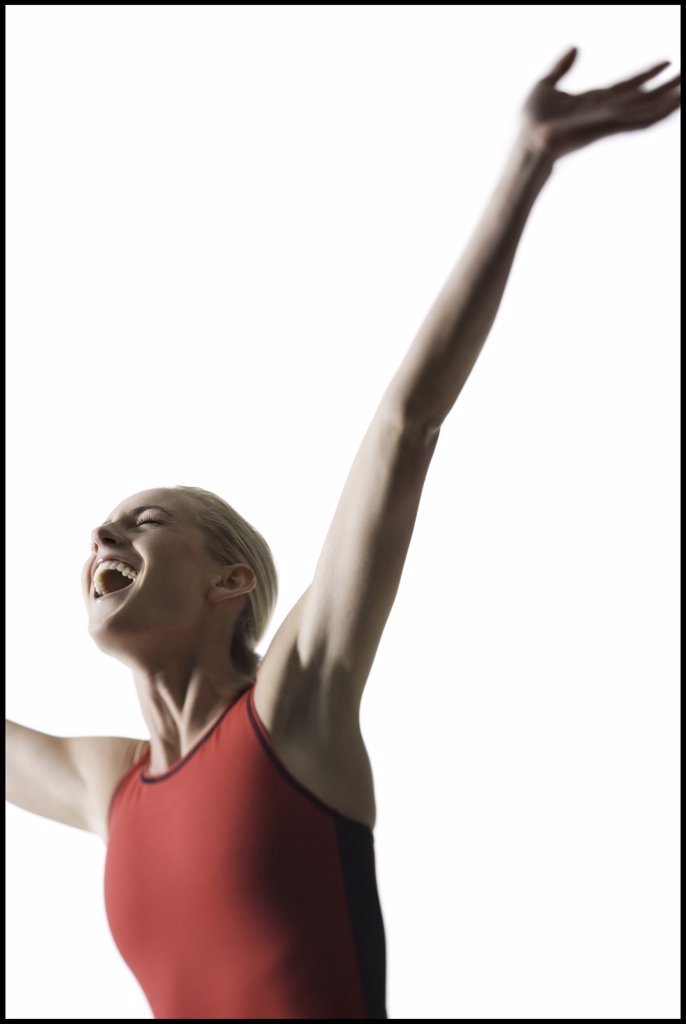 Low angle view of a young woman smiling with her arms raised : Stock Photo