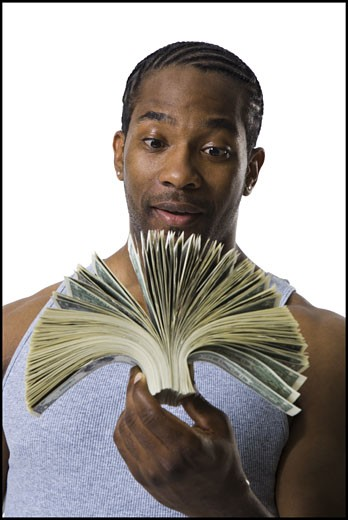 African American holding a pile of dollar bills : Stock Photo
