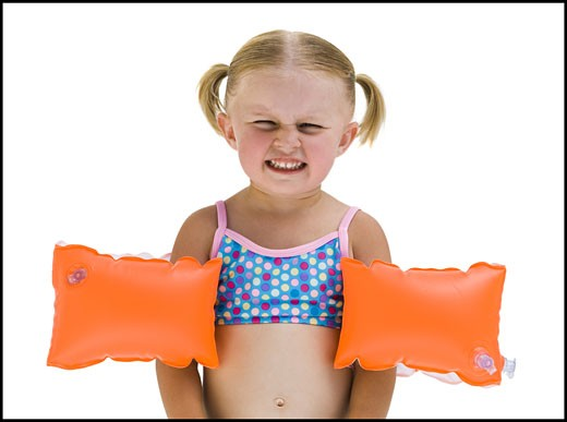 Stock Photo: 1660R-14475 Young girl with personal flotation devices around arms