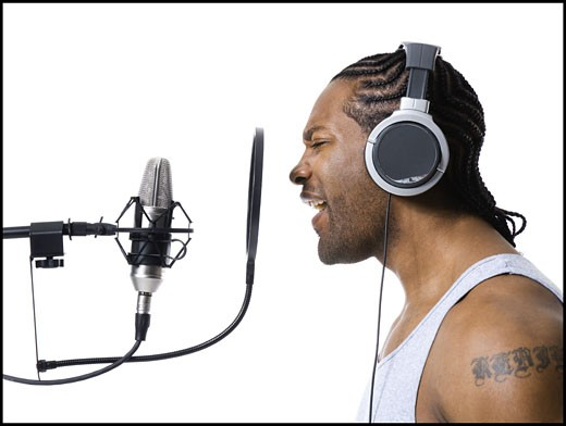 Stock Photo: 1660R-14560 African American man singing into microphone