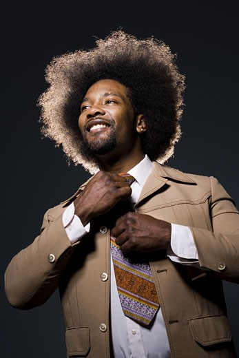 Stock Photo: 1660R-14652 Man with an afro in beige suit adjusting necktie