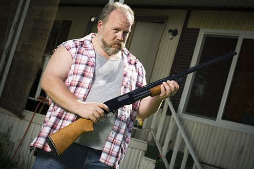 Stock Photo: 1660R-14870 Overweight man with a shotgun