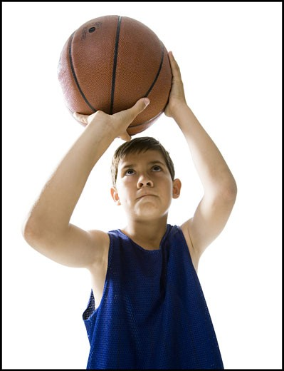 Boy playing basketball and taking a shot : Stock Photo