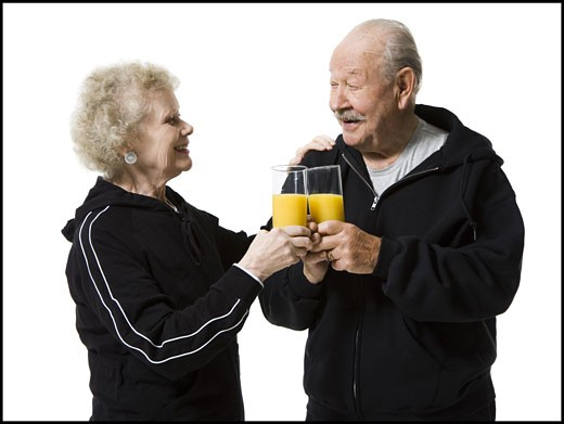 Older couple in track suits taking a juice break : Stock Photo