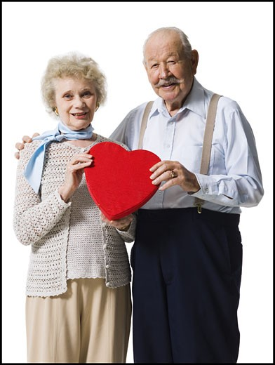 Older man giving wife Valentines chocolate : Stock Photo