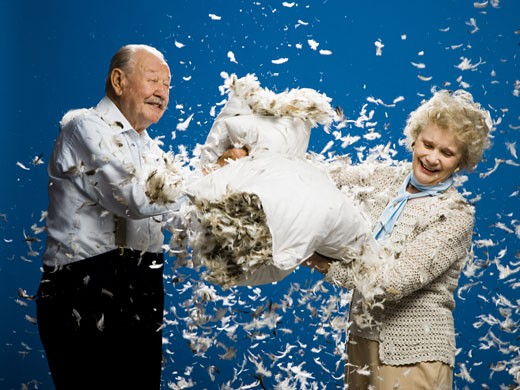 Stock Photo: 1660R-15489 Older couple pillow fighting