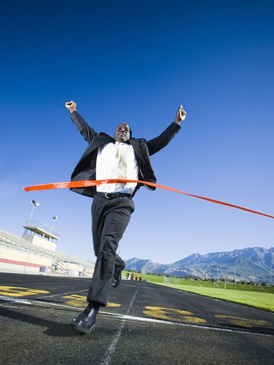 Businessman running and crossing finish line : Stock Photo