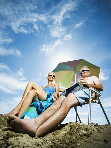 Mature couple at the beach relaxing on deck chairs : Stock Photo