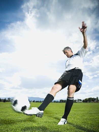 Stock Photo: 1660R-15679 Soccer player kicking ball