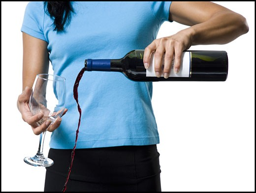 Stock Photo: 1660R-15734 Distracted woman pouring red wine and missing glass
