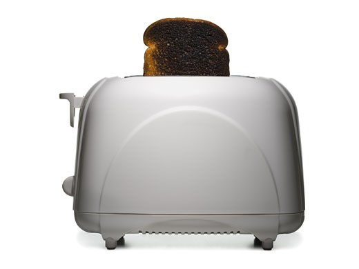 Slice of burnt toast in a toaster : Stock Photo