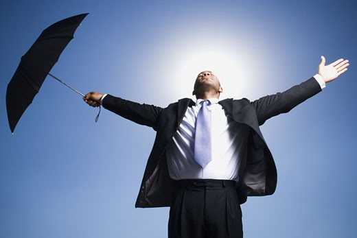 Businessman holding umbrella on a clear day : Stock Photo