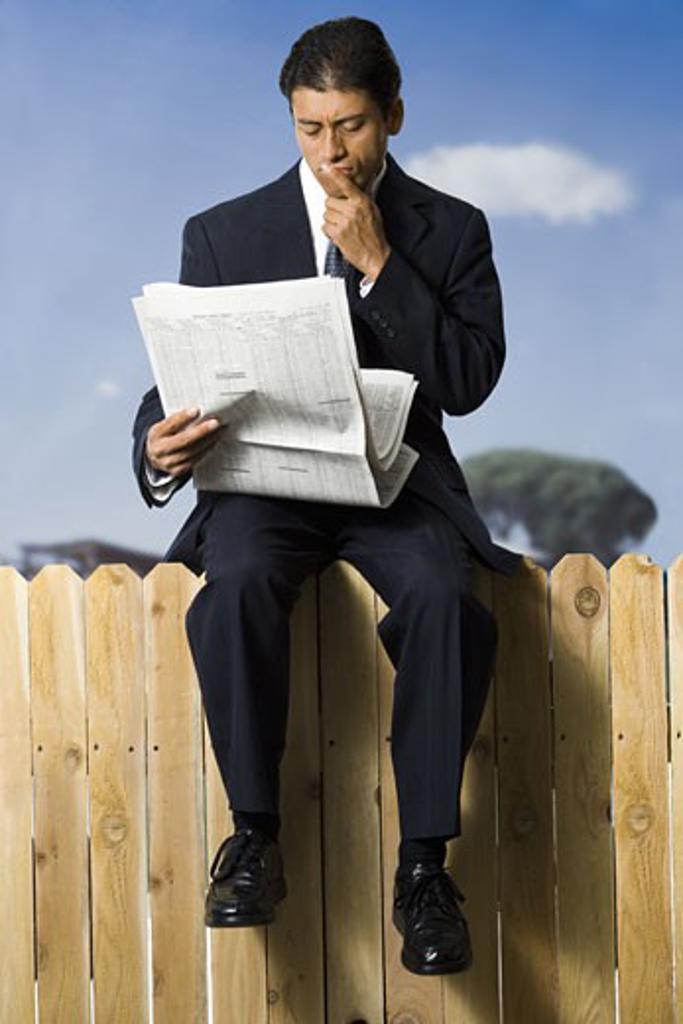 Businessman sitting on fence reading newspaper : Stock Photo