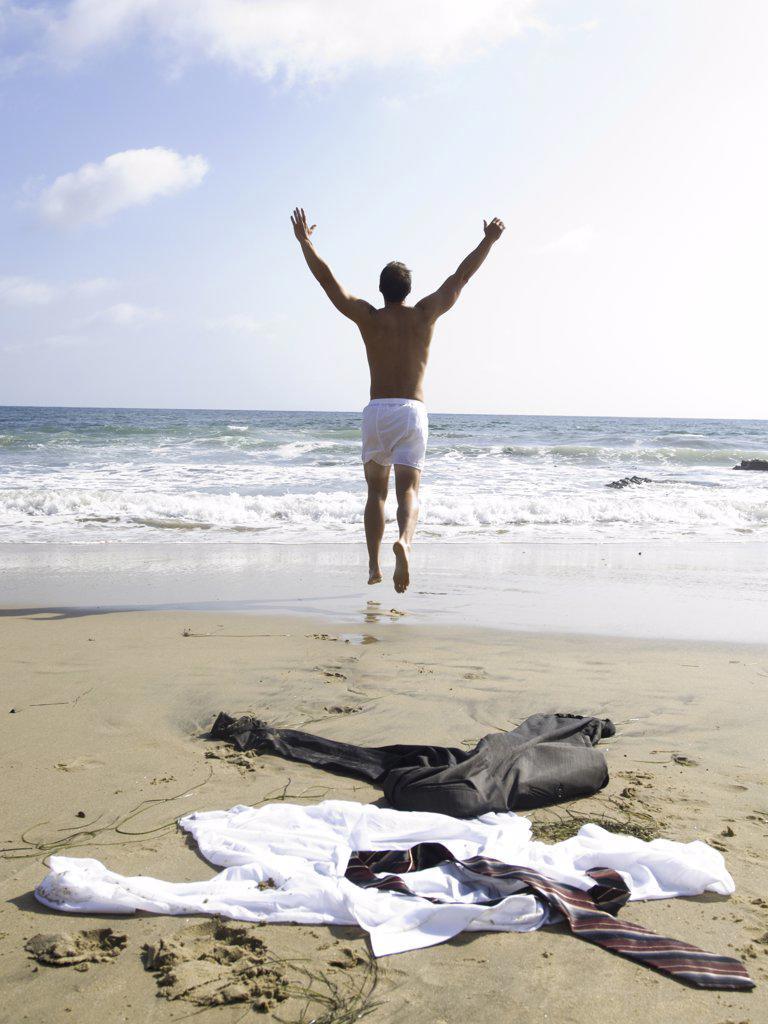 Stock Photo: 1660R-16774 Man in underwear running to water with business attire on sandy beach