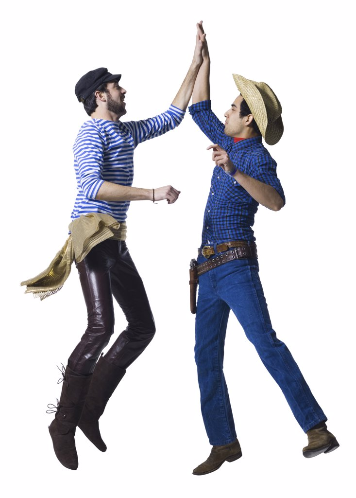 Man in cowboy costume and man in leather pants with waist sash high five : Stock Photo