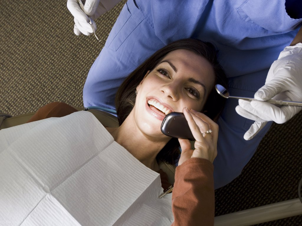 Stock Photo: 1660R-16959 Woman with dental hygienist talking on cell phone